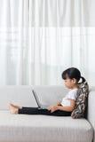 说谎在有膝上型计算机的沙发的亚裔中国小女孩 免版税库存图片