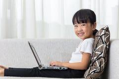 说谎在有膝上型计算机的沙发的愉快的亚裔中国小女孩 免版税图库摄影