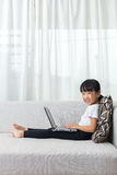 说谎在有膝上型计算机的沙发的愉快的亚裔中国小女孩 库存照片