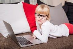 戴说谎在有膝上型计算机的长沙发的眼镜的孩子在她前面 库存照片
