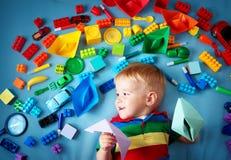 说谎在有许多玩具的毯子的男婴 免版税库存照片