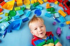 说谎在有许多玩具的毯子的男婴 图库摄影
