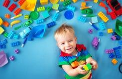 说谎在有许多玩具的毯子的男婴 免版税图库摄影