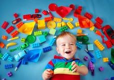 说谎在有许多玩具的毯子的男婴 免版税库存图片