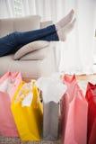 说谎在有购物袋的长沙发的妇女 免版税库存照片