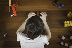 说谎在木地板上和使用与五颜六色的玩具的小男孩顶视图 免版税库存图片