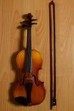 说谎在木地板上的小提琴和打破的弓 免版税库存照片