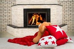 说谎在枕头,盖用毯子和观看火的火焰的在壁炉的玩具熊 图库摄影