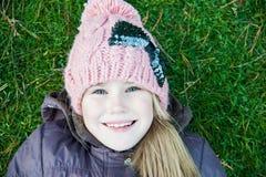 说谎在桃红色帽子,冷的季节,特写镜头画象的绿草的微笑的小女孩 库存图片
