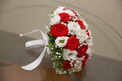 说谎在桌上的红色和白玫瑰婚礼花束  免版税库存图片