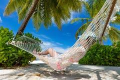 说谎在棕榈之间的吊床的妇女在一个热带海滩 Maldiv 免版税库存照片