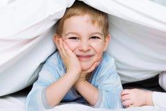 说谎在毯子下的逗人喜爱的小男孩 库存图片