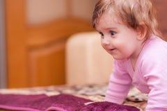 说谎在毯子和显示舌头的小婴孩 免版税库存照片