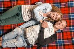 说谎在毯子和看天空的爱恋的夫妇 免版税图库摄影