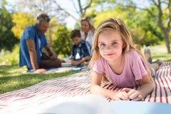 说谎在毯子和阅读书的女孩,当坐在背景中时的家庭 免版税库存图片