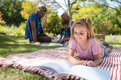 说谎在毯子和阅读书的女孩,当坐在背景中时的家庭 免版税库存照片