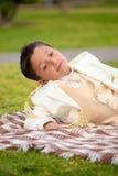 说谎在毯子的年轻人第一个圣餐男孩户外 库存照片