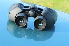 说谎在汽车敞篷的双筒望远镜。 免版税图库摄影