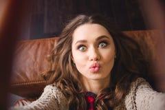 说谎在沙发和做selfie照片的妇女 免版税库存照片