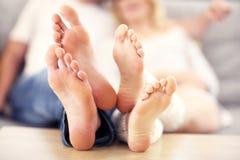 说谎在沙发的一对愉快的夫妇的Barefeet 免版税库存图片
