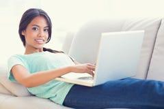 说谎在沙发的俏丽的女孩使用她的微笑对照相机的膝上型计算机 库存图片