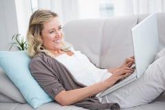 说谎在沙发的俏丽的妇女使用她的膝上型计算机 库存照片