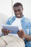 说谎在沙发的偶然人使用他的片剂个人计算机 免版税库存图片