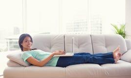 说谎在沙发的女孩使用她的微笑对照相机的膝上型计算机 免版税库存图片