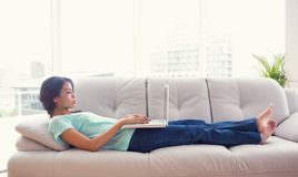 说谎在沙发的女孩使用她的膝上型计算机 图库摄影
