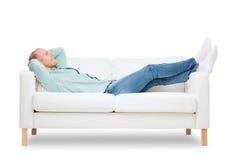 说谎在沙发的微笑的人 免版税库存照片