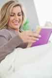 说谎在沙发的微笑的妇女读书 库存图片
