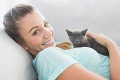 说谎在沙发的快乐的妇女拥抱一只灰色小猫 库存照片