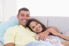 说谎在沙发的愉快的夫妇 免版税库存图片
