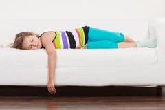 说谎在沙发的疲乏的被用尽的懒惰小女孩孩子 库存照片