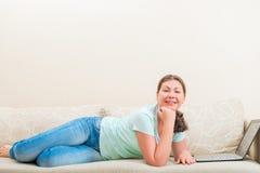 说谎在沙发的美丽的无忧无虑的女孩 免版税图库摄影