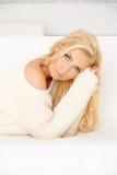 说谎在沙发的美丽的白肤金发的妇女 免版税库存图片