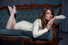 说谎在沙发的年轻可爱的深色的妇女 免版税库存图片