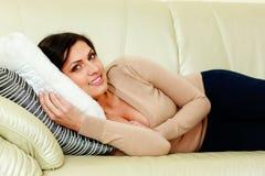 说谎在沙发的年轻愉快的微笑的妇女 免版税图库摄影