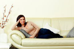 说谎在沙发的年轻愉快的微笑的妇女 免版税库存图片