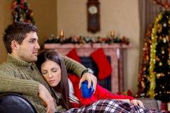 说谎在沙发的年轻浪漫夫妇在圣诞夜 免版税库存照片