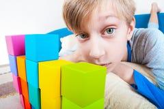 说谎在沙发的滑稽的小男孩使用与五颜六色的立方体 免版税图库摄影