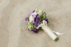 说谎在沙子的新娘花束 免版税库存照片