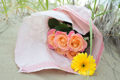 说谎在沙子的玫瑰和黄色大丁草花束  库存图片