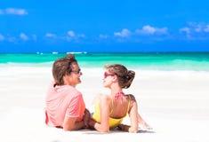 说谎在沙子的年轻夫妇在晴朗的夏天太阳下 免版税图库摄影