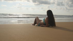 说谎在海海滩的金黄沙子和放松在暑假旅行期间的比基尼泳装的美丽的少妇 晒黑 免版税库存照片