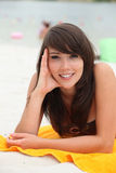 说谎在海滩毛巾的妇女 免版税库存图片