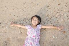 说谎在海滩沙子的亚洲人微笑的逗人喜爱的小女孩 泰国池氏 免版税库存照片