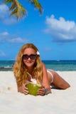 说谎在海滩的女孩用椰子在他的手上 免版税库存图片