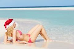 说谎在海滩的妇女戴圣诞老人帽子 库存图片