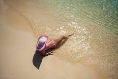 说谎在海滩的帽子的俏丽的妇女 库存图片